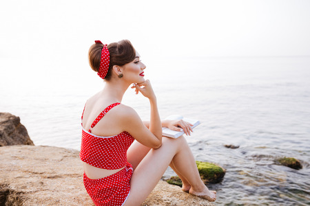 Young beautiful pensive pin up girl sitting with book on the rock at the beach Stock Photo