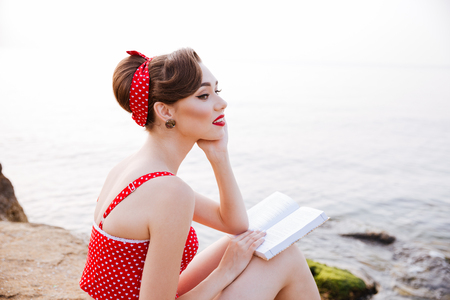 Young beautiful pensive pin up girl sitting with book on the rock at the beach Stok Fotoğraf