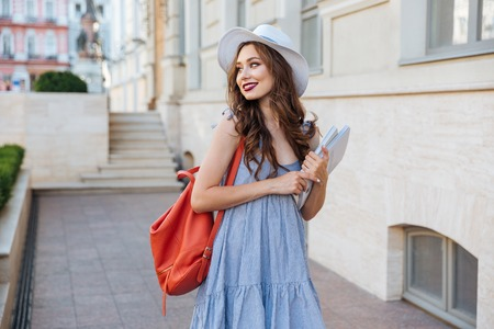 cheeful: Cheeful attractive young woman with red backpack and book walking in the city