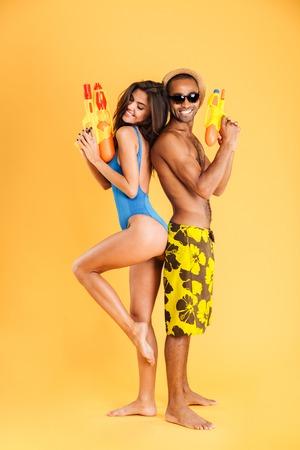 Paar dat zich rijtjes klaar voor een duel van het waterpistool bevindt dat op de oranje achtergrond wordt geïsoleerd