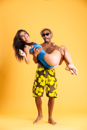 Afro american man holding his girlfriend with two hands isolated on orange background Imagens