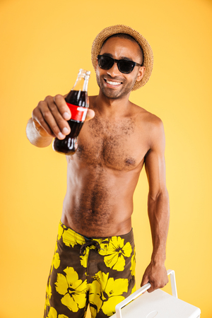 coke bottle: Cheerful young man in hat and sunglasses holding coke bottle and cooler bag over orange background