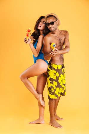 woman squirt: Couple standing back to back ready for a water pistol duel isolated on the orange background