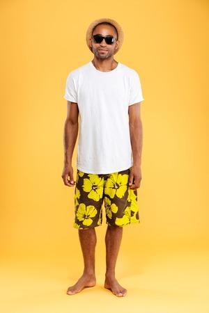 Portrait der attraktiven jungen afrikanischen Mann in Hut und Sonnenbrille über orange Hintergrund