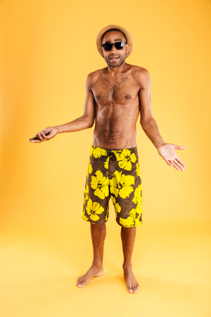 Confused young handsome african man talking on cell phone isolated on a orange background