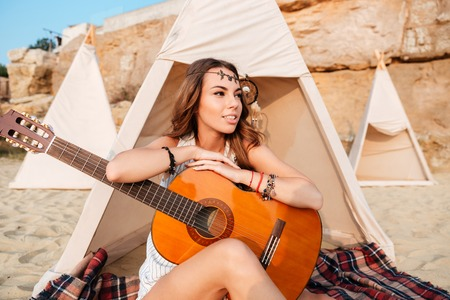 mujer hippie: Smiling young hippie woman posing with guitar at the beach tent Foto de archivo