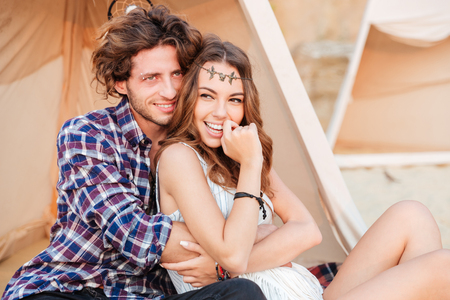 Happy young couple in love sitting in wigwam on the beach