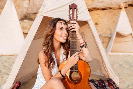 Happy charming young woman sitting and holding guitar in wigwam on the beach