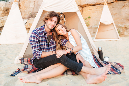 romantic beach: Smiling young couple relaxing and hugging in wigwam on the beach Stock Photo
