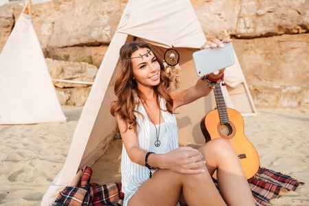 Happy young woman taking selfie with smartphone in wigwam on the beach