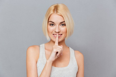 noiseless: Potrait of smiling attractive young woman showing silence gesture over gray background