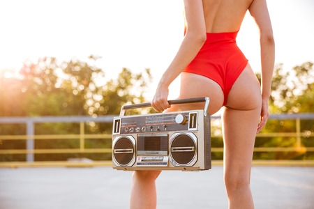 Back view of alluring young woman in red swimsuit standing outdoors and holding old boombox