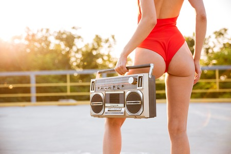 Back view of a girl in red swimsuit on roller skates holding old record player on the open road outdoors Stock Photo