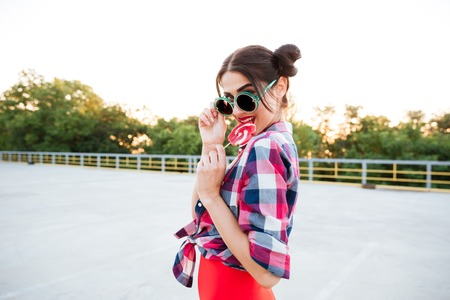 Happy attractive young woman in round sunglasses eating lollipop outdoors Stock Photo