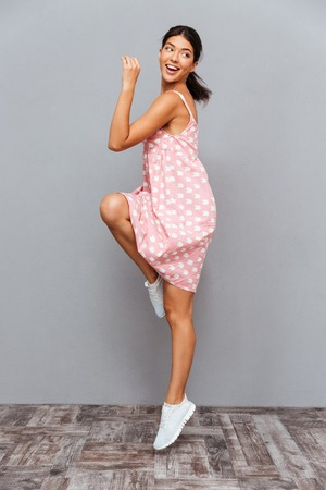 Full length portrait of a cheerful woman celebrating her success isolated on a gray background Stock Photo