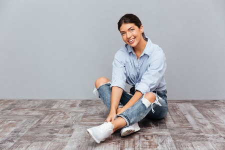 feminity: Portrait of a smiling young girl sitting on the floor isolated on a gray background Stock Photo