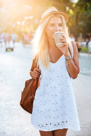 looking away from camera: Young beautiful blonde girl in hat drinking coffee from take away cup while walking on the street