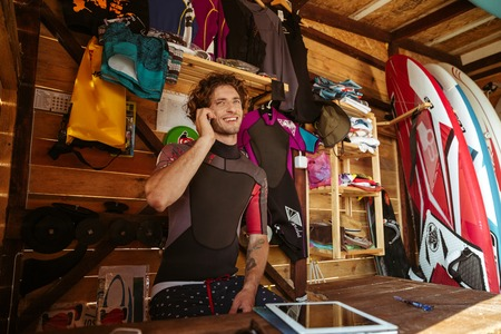 surf shop: Smiling young man in swimsuit talking on smartphone while sitting in the surf shack