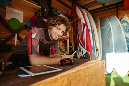 shack: Smiling young man in swimsuit using smartphone while sitting in the surf shack