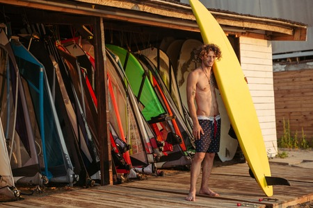 bodyboarding: Full length of handsome curly man surfer standing and holding yellow surfing board