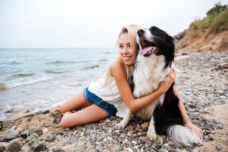 Sonriente joven encantadora abrazando a su perro en la playa Foto de archivo