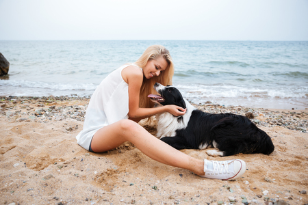 Happy attractive young woman having fun with her dog on the beach