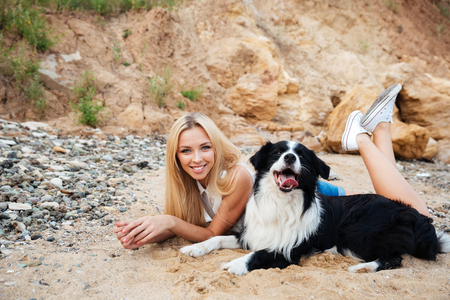 Happy charming young woman with dog lying and smiling on the beach 写真素材
