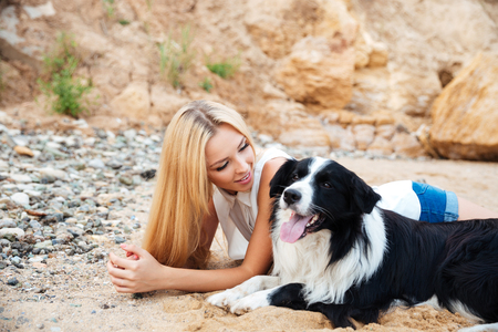 unrecognisable people: Happy charming young woman lying and looking at her dog on the beach