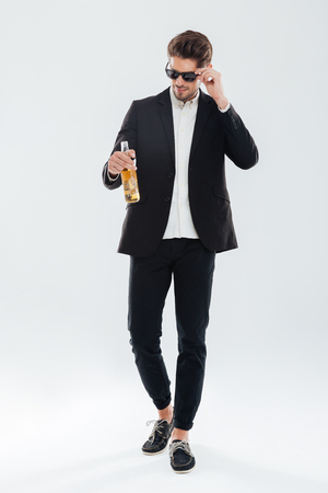habbit: Full length portrait of a handsome serious businessman in black sunglasses holding beer bottle over gray background Stock Photo