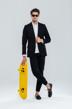 legs crossed: Serious young businessman in sunglaasses and suit leaning on skateboard with legs crossed over gray background