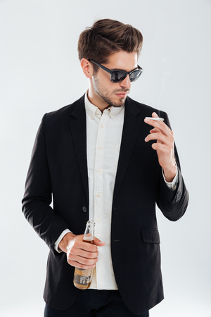 habbit: Young handsome businessman in sunglasses holding beer bottle and smoking cigarette over gray background