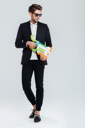 Attractive young handsome businessman in suglasses and suit holding water gun over gray background Stock Photo
