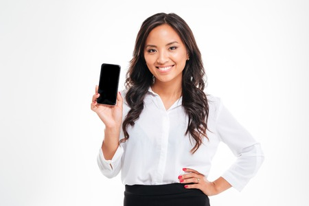 Smiling businesswoman showing blank smartphone screen over white background Фото со стока