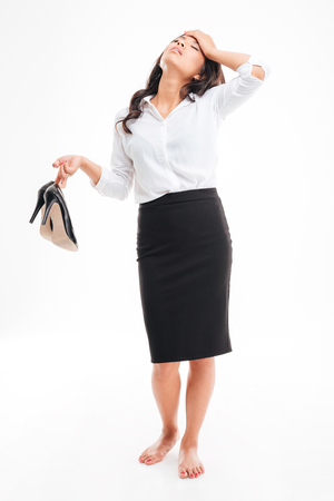 Tired exhausted young asian businesswoman standing barefoot and holding high heels shoes over white background