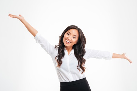 Portrait of a happy asian busineswoman with raised hands up over white background