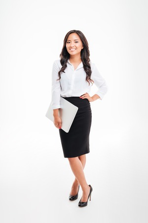 Full length portrait of a smiling asian businesswoman holding laptop isolated on a white background