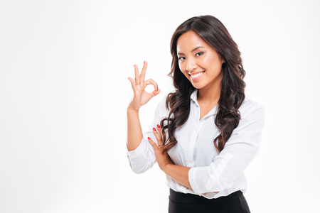 copyspace: Happy young asain businesswoman showing ok sign isolated on a white background