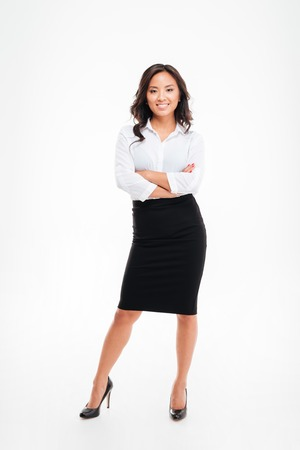 Full length portrait of a smiling asian businesswoman standing with arms folded isolated on a white background Stock Photo