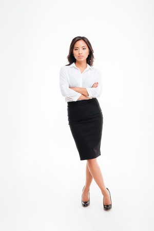 legs folded: Full length portrait of a serious asian businesswoman standing with arms folded and legs crossed isolated on a white background