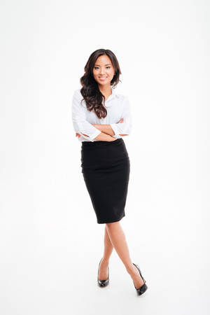 legs folded: Full length portrait of a smiling asian businesswoman standing with arms folded and legs crossed isolated on a white background Stock Photo