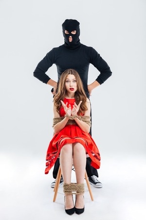 ful: Ful length of man in balaclava and frightened young woman sitting bounded with ropes Stock Photo