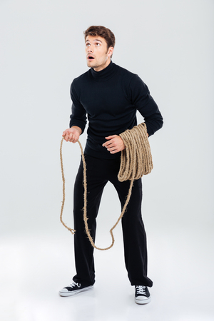 Full length of amazed young man with rope standing and looking up Stock Photo