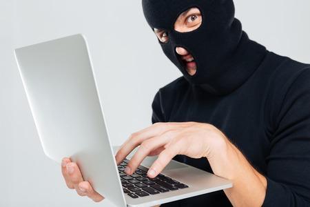 furtive: Closeup of criminal man in balaclava using laptop