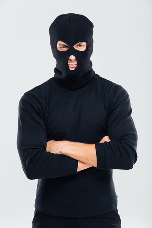felonious: Portrait of man in balaclava standing with arms crossed Stock Photo