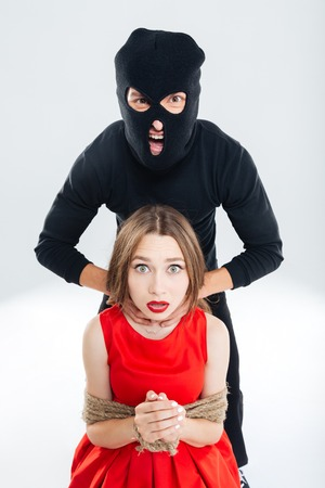 bounded: Woman bounded with ropes choking by cryminal man in balaclava