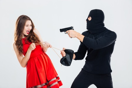theif: Man theif in balaclava threatening with gun and stealing young woman bag Stock Photo