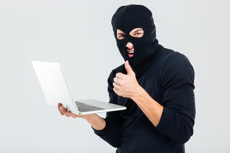 looter: Man in balaclava using laptop and showing thumbs up Stock Photo