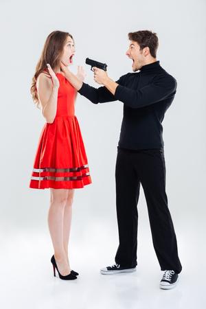 Volledige lengte van strafbare man verstikking en dreigt met pistool aan vrouw