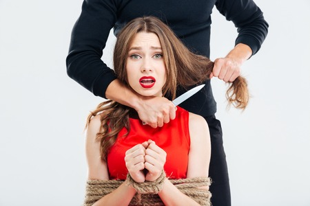 threatened: Scared young woman bounded with ropes threatened by criminal man with knife Stock Photo