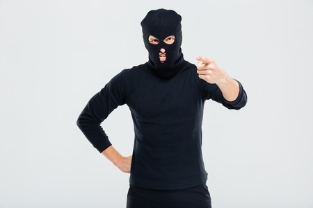 rowdy: Mad irritated young man in balaclava standing and pointing on you